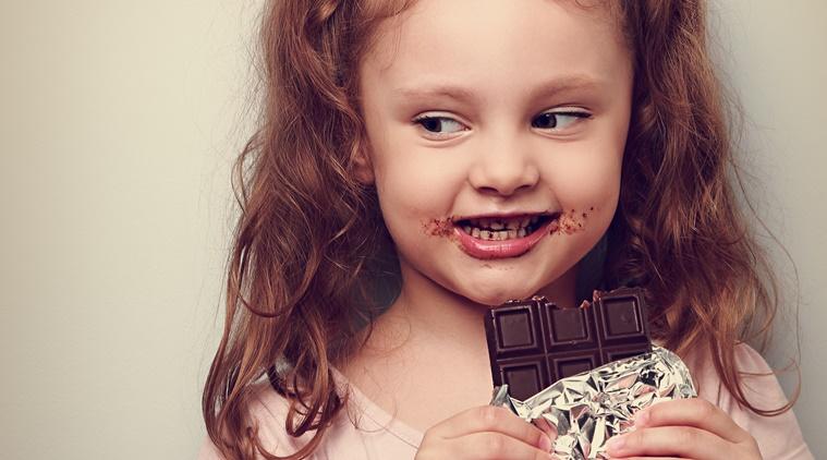 Curious cute kid girl eating dark chocolate and looking fun